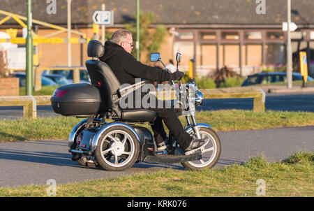 Man riding a 3 wheeled electric disabled mobility scooter in the UK. - Stock Photo