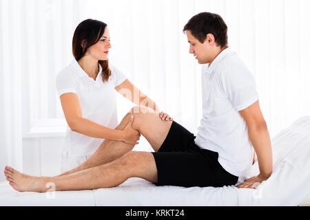 Therapist Massaging Man's Leg - Stock Photo