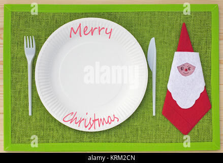 knife,fork,napkin and paper plates on green placemat and lettering merry christmas - Stock Photo