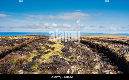 Peat bog with sods of cut turf for fuel left out to dry near Bloody Foreland, County Donegal, with Tory Island in - Stock Photo