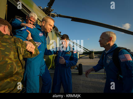 Expedition 47 astronaut Tim Kopra of NASA is helped from the helicopter that brought him to the Karaganda Airport - Stock Photo