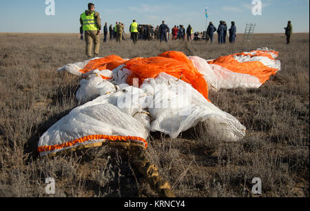 Russian support personnel work around the Soyuz MS-02 spacecraft shortly after it landed with Expedition 50 Commander - Stock Photo
