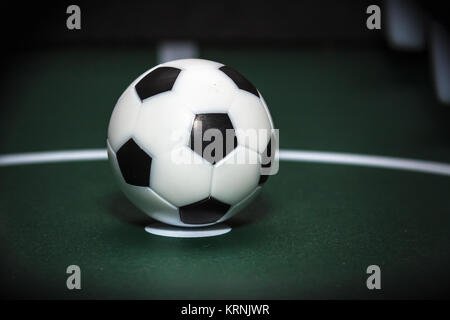 Soccer table game. Green field and plastic ball on it. Sport background - Stock Photo
