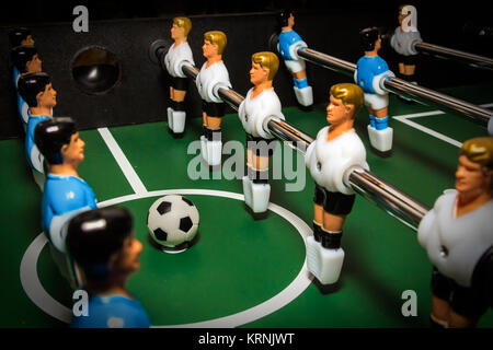 Soccer table game. Green field with blue and white plastic footballers. Sport background - Stock Photo