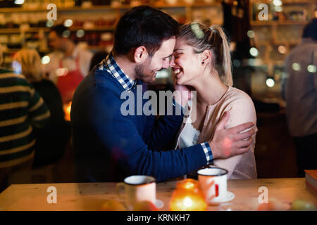 Happy couple kissing at bar and having date - Stock Photo