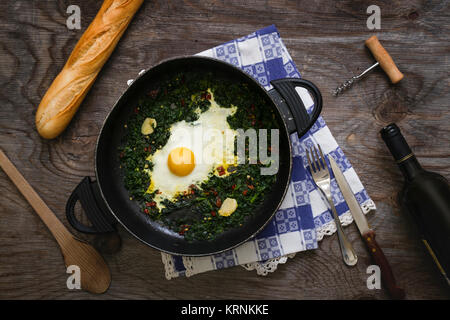 Fried eggs and spinach in a pan - Stock Photo