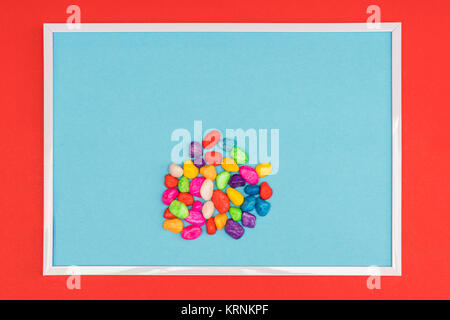 colored pebbles in a white frame on a colored background - Stock Photo