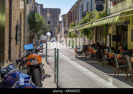 Quiet sunny street in Aigues-Mortes with outdoor cafe, and tower of town walls in the background. Aigues-Mortes, - Stock Photo