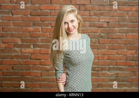 Portrait of a blonde in a light sweater. Standing against the red brick wall background, smiling and posing for - Stock Photo