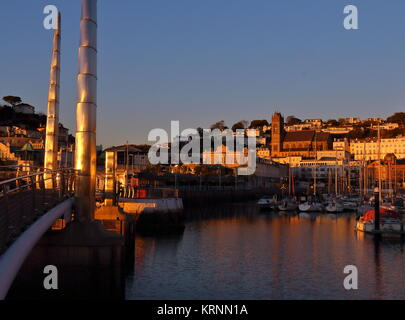 Evening sunshine golden over Torquay harbour with harbour footbridge in foreground, looking towards St John's Church. - Stock Photo