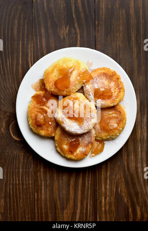 Curd cheese pancakes with caramelized apple slices on wooden table. Top view, flat lay. - Stock Photo
