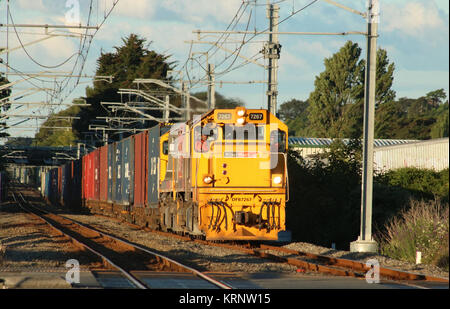 Double headed diesel-electric locomotives in KiwiRail livery head south through Paraparaumu with freight train on - Stock Photo