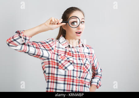 woman looks through a magnifying glass - Stock Photo