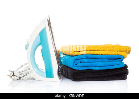iron and clothes.  Steam iron and colored towels isolated on white background - Stock Photo