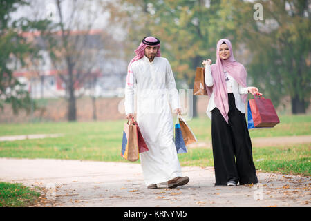 Lovely muslim couple taking a walk after shopping. concept - Stock Photo