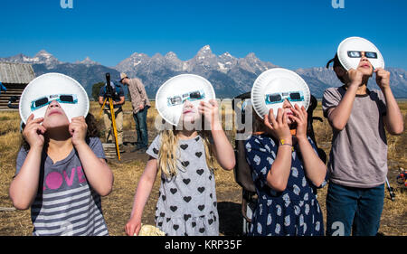 Group of children look up wearing eclipse glasses to watch Solar Eclipse, Grand Tetons National Park, Teton County, - Stock Photo