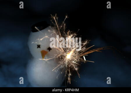 A little cute snowman with a sparkler in dark night - Stock Photo