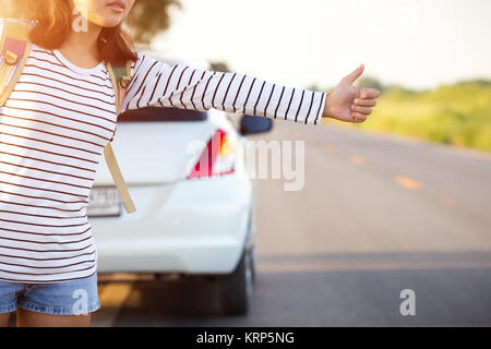 woman hitchhiking looking for help with her broken car on the road - Stock Photo