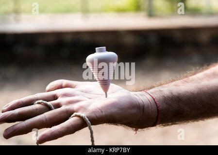 Spinning top on hand - traditional toy in Rajkot, Gujarat, India - Stock Photo