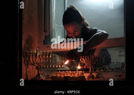 A religious Jewish woman lights an olive oil candle on a menorah candelabrum placed on the windowsill of her house - Stock Photo