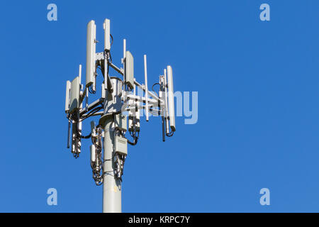 3 sector cellular telecom communications panel antenna array for the mobile telephone system on a cellsite pole - Stock Photo