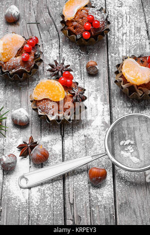 little cupcakes in tins ,decorated with berries and a slice of tangerine - Stock Photo