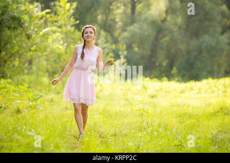 Young beautiful woman walking on a green meadow with a bouquet of wildflowers in a light summer dress - Stock Photo