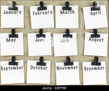 Monthly notes clipped on noticeboard - Stock Photo