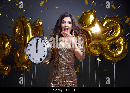 Excited woman holding clock during new year's photo session - Stock Photo