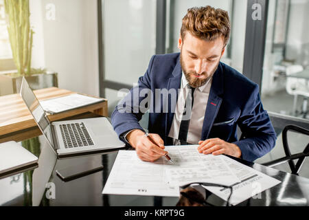 Tax manager working at the office - Stock Photo