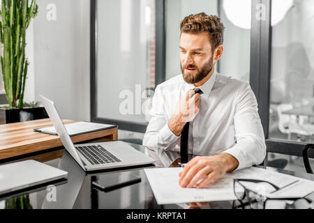Tired tax manager working at the office - Stock Photo