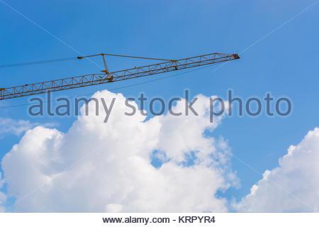 Baumaschine auf einer Baustelle im Hintergrund ein blauer Himmel. - Stock Photo