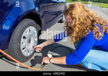 Female car driver checking air pressure of tire outside - Stock Photo