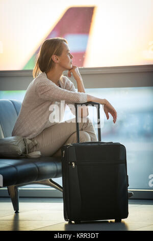 Young female passenger at the airport, waiting for her flight boarding call (color toned image  shallow DOF) - Stock Photo