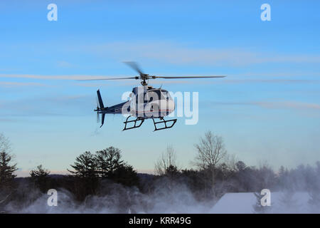 An emergency evacuation helicopter coming in for a landing in Speculator, NY USA in winter. - Stock Photo