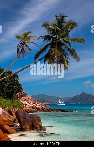 Granite boulders on the shore at Anse Severe , Palm trees, sailing boat, La Digue, Praslin in the back, Seychelles, - Stock Photo