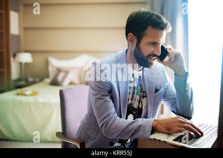 Portrait of successful young handsome man using laptop - Stock Photo