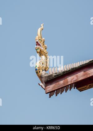 Wooden dragon head from the carving in the traditional northern Thai style on the eaves of the church. - Stock Photo