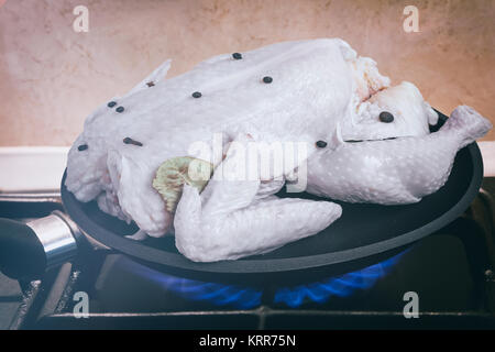 On fire gas stove a frying pan with the chicken prepared for roasting. Presents closeup. - Stock Photo