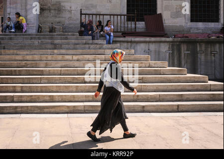 Turkish woman wearing headscarf walking along street past steps of a mosque in Istanbul Turkey - Stock Photo