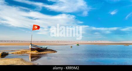 Boat on Chott el Djerid, an endorheic salt lake in Tunisia - Stock Photo