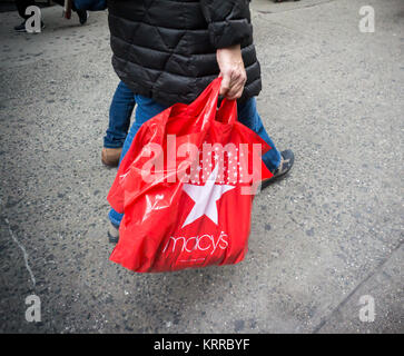 Shoppers with their Macy's purchases in Herald Square in New York on Tuesday, December 12, 2017. Only 12 more shopping - Stock Photo