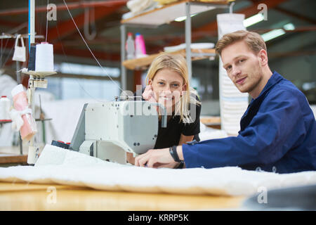 Seamstress is new assigned to a machine in a textile factory, the foreman explains something - Stock Photo