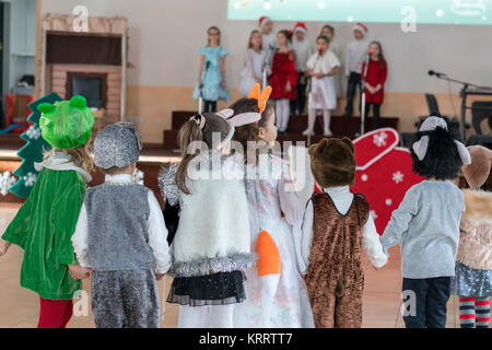 children's music groups sing and dance at the graduation concert. Children in front of their parents show what they - Stock Photo