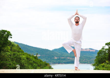 Man Doing Indian classic Yoga at the Sea and Mountains - Stock Photo