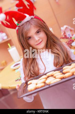 Little girl making Christmas cookies - Stock Photo