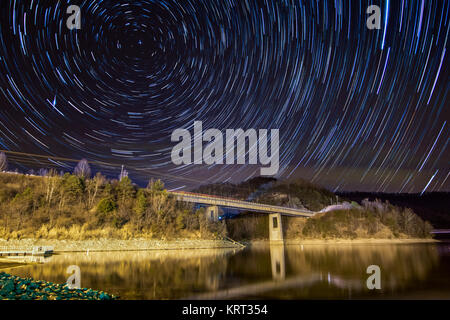 Star trails reveal the rotation of the earth above the surface of a lake. - Stock Photo