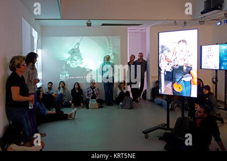 Visitors watching photography and video installation by Israeli artist Rona Feyman which documents her long-term - Stock Photo