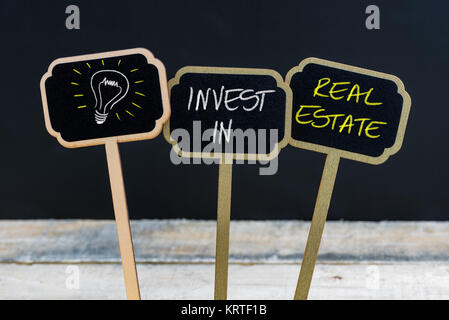 Concept message INVEST IN REAL ESTATE and light bulb as symbol for idea - Stock Photo