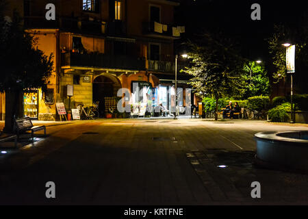 Late night at Garibaldi Square, the main town square of Monterosso Al Mare, Cinque Terre, with a few locals in front - Stock Photo